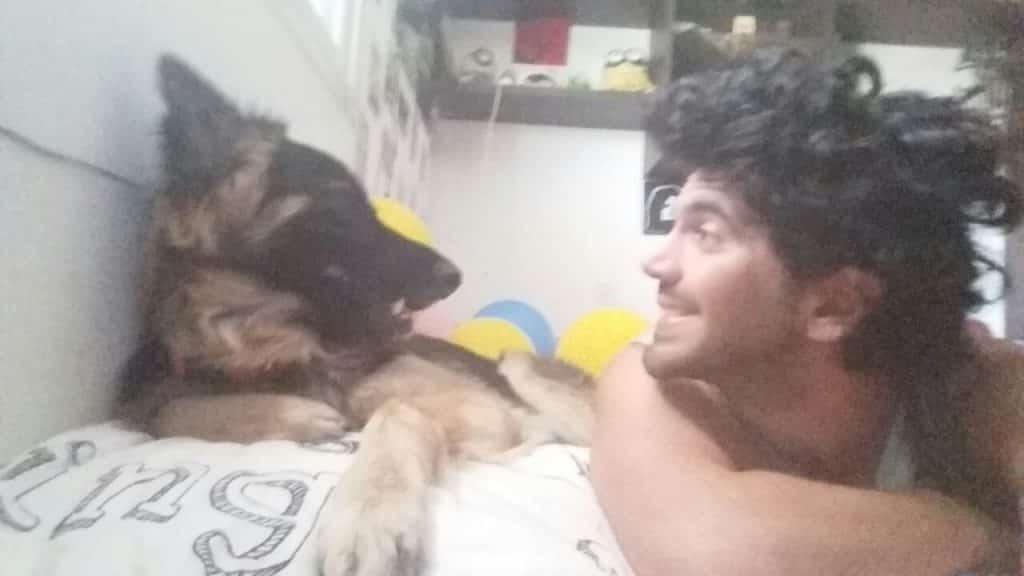 גל בומנדיל בוגר מחזור כלבנות 2016 מצולם שוכב על מיטתו עם הכלב שלו פו שאומץ מהעמותה